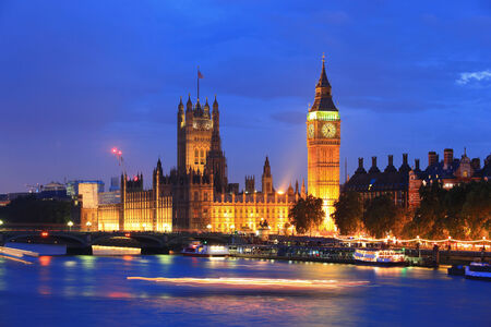 Big Ben and Houses of Parliament with blur ships on thames river at night, London, United Kingdom, UK photo