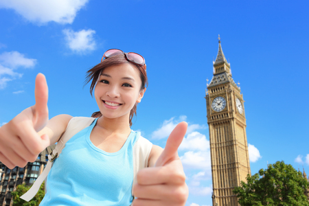 Happy woman travel in London with Big Ben tower, she show thumbs up and smile to you, asian photo