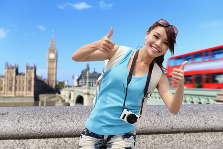 Happy travel woman show thumb up in London with Big Ben tower,  London, UK,  asian beauty photo