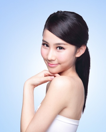 Beautiful Skin care woman Face smile to you isolated on blue background. asian Beauty photo
