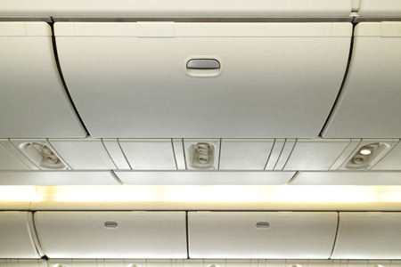 compartments: Commercial aircraft interior in airplane cabin, Overhead compartment