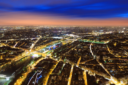 Aerial Night view of Paris City and Seine river shot on the top of Eiffel Tower