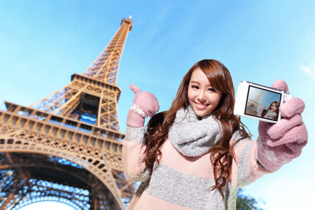 Happy travel woman take a selfie by camera with eiffel tower in Paris with blue sky Stock Photo