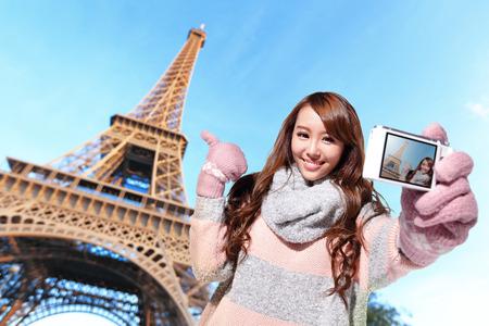Happy travel woman take a selfie by camera with eiffel tower in Paris with blue sky Zdjęcie Seryjne