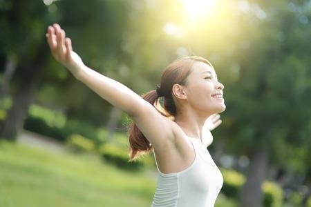 livsstil: Carefree och fri jublande kvinna i parken. Flickan höja armarna upp ler lyckligt. asiatisk skönhet
