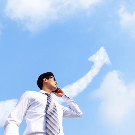 ganador: El �xito de concepto del hombre de negocios - hombre de negocios hablando por tel�fono inteligente con un crecimiento flecha nube en el cielo Foto de archivo