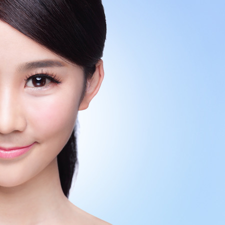 skin care woman: Half of Beautiful Skin care woman Face smile to you isolated on blue background. asian Beauty
