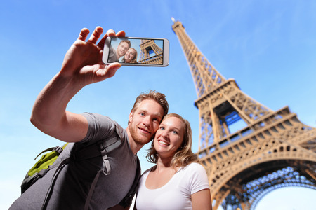happy couple selfie by smart phone in Paris with eiffel tower, caucasian Standard-Bild