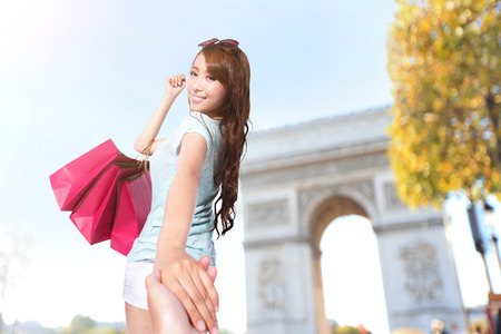 Happy Shopping in Paris - beautiful young woman holding colored shopping bags with Arc de Triomphe