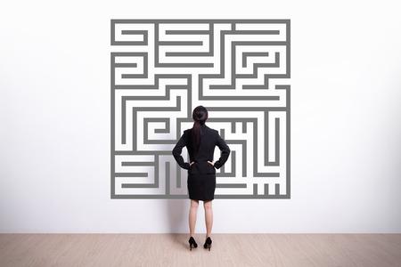 Achter mening van het bedrijfsleven vrouw kijkt doolhof met witte muur achtergrond, Aziatische