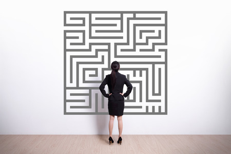 maze game: Back view of business woman look maze with white wall background, asian