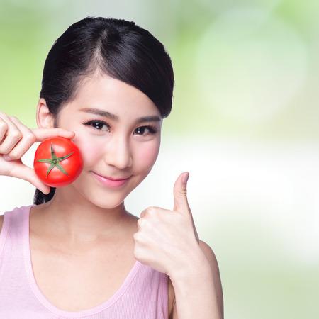 Gezondheid meisje toont tomaat met glimlach gezicht, health food concept, Aziatische vrouw schoonheid Stockfoto