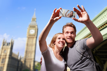 london big ben: happy couple selfie by smart phone in london with big ben background, caucasian