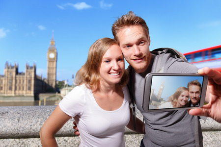 traveller: happy couple selfie by smart phone in london with big ben background, caucasian