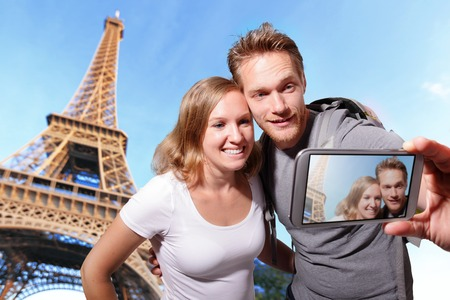 happy couple selfie by smart phone in Paris with eiffel tower, caucasian photo