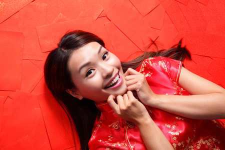 red envelope: happy chinese new year. Smile woman lying on red envelope bed, high angle view