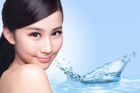 fresh face: Concetto di bellezza Cura della pelle, Bella donna faccia con schizzi d'acqua isolato su sfondo blu, modello asiatico
