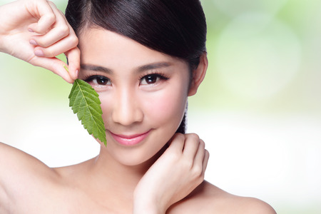 skin care: beautiful woman face portrait with green leaf , concept for skin care or organic cosmetics , asian beauty