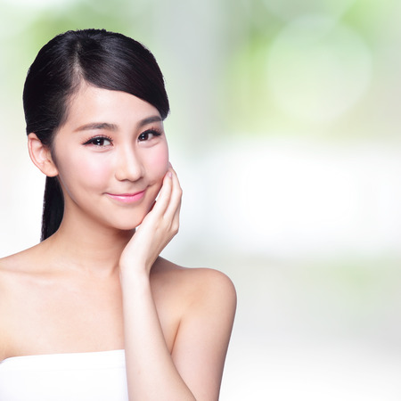 girl care: Beautiful Skin care woman Face smile to you with nature green background. asian Beauty