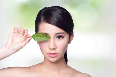 beautiful woman face portrait with green leaf , concept for skin care or organic cosmetics , asian beauty photo