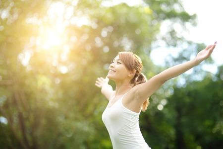 Zorgeloos en vrij gejuich vrouw in het park. meisje verhogen haar armen omhoog glimlachen gelukkig. Aziatische schoonheid