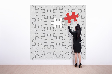 solves: business woman hold jigsaw puzzle - Back view of business woman making a puzzle on the wall Stock Photo