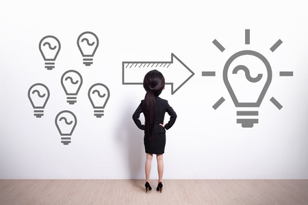 idea and innovation concept - Back view of business woman look light bulb - big head cute woman photo