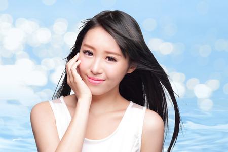 human skin: Concepto de la belleza Cuidado de la piel, la cara de mujer hermosa y pelo largo con salpicaduras de agua aisladas sobre fondo azul, modelo asi�tico Foto de archivo