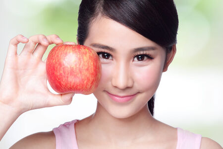 asian foods: Beautiful young woman hold red apple with charming smile. Isolated over nature green background, asian beauty