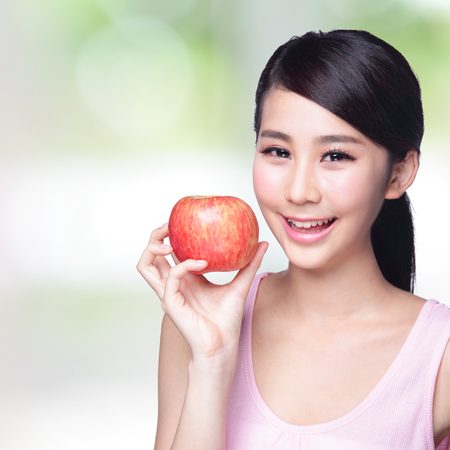 Beautiful young woman hold red apple with charming smile. Isolated over nature green background, asian beauty