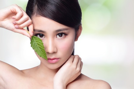 moisturizers: beautiful woman face portrait with green leaf , concept for skin care or organic cosmetics , asian beauty