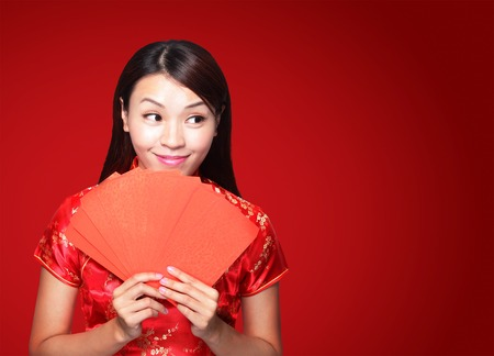 red envelope: happy chinese new year. smile asian woman holding red envelope isolated on red background Stock Photo