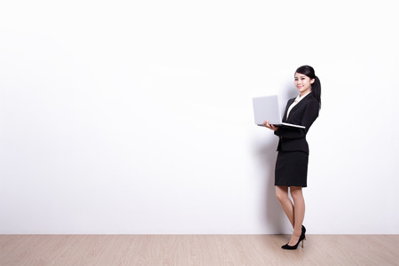 business woman using laptop computer with white wall background, great for your design or text, asian photo