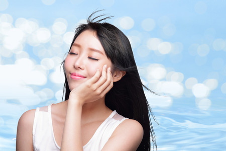 Beauty Skin care concept, Beautiful woman face and long hair with Water splashes blue background, asian beauty