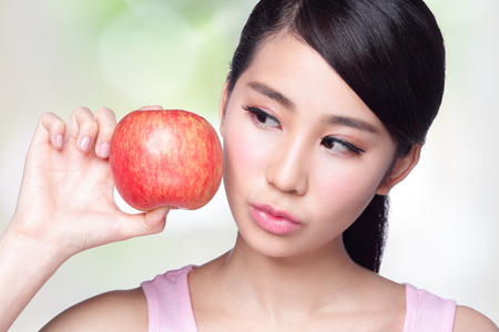 건강 생활 개념 - 아름 다운 젊은 여자는 미소와 함께 빨간 사과를 개최합니다. 자연 녹색 배경에 고립, 아시아 스톡 콘텐츠