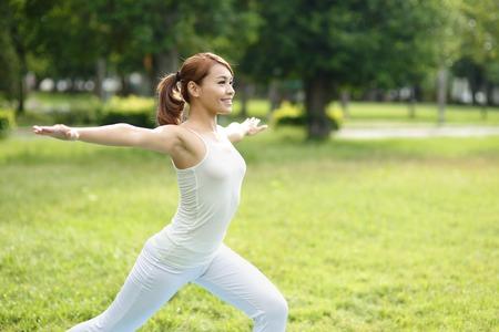 ヤング スポーツ公園で女の子を行うヨガ アジアの美しさの女性