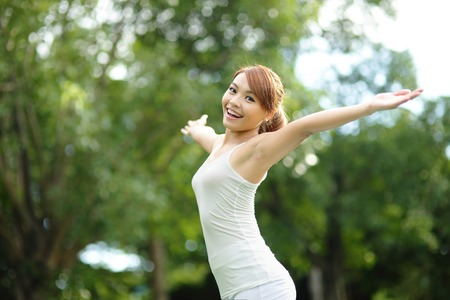 chinese woman: Carefree and free cheering woman in the park. girl raising her arms up smiling happy. asian beauty