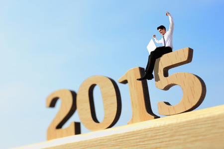 Happy new year for 2015 - success business man with laptop computer and sitting on wood number photo