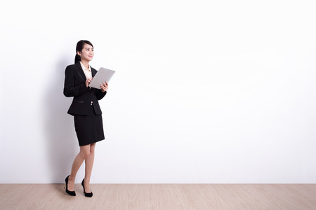 business woman using digital tablet pc computer with white wall background, great for your design or text, asian
