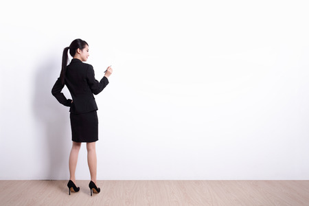 Back view of business woman writing something on white wall background, great for your design or text, asian
