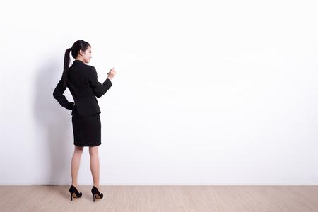 alzando la mano: Volver la vista de mujer de negocios escrito algo en el fondo de la pared blanca, perfecto para su diseño o texto, asiático Foto de archivo