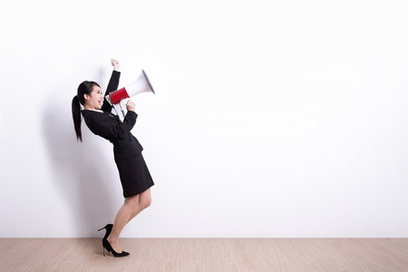 business woman talking in megaphone with white wall background, great for your design or text, asian Foto de archivo