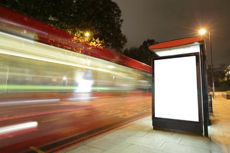 parada de autobus: Cartelera en blanco en la parada de autobús en la noche con las luces de los coches que pasan por, gran espacio de la copia para su diseño, rodada en Londres, Reino Unido, Reino Unido