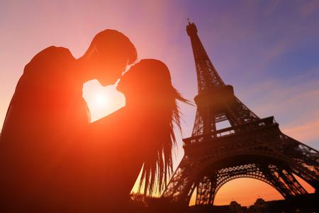 romance: sylwetka romantycznych kochanków z wieży Eiffla w Paryżu z zachodem słońca