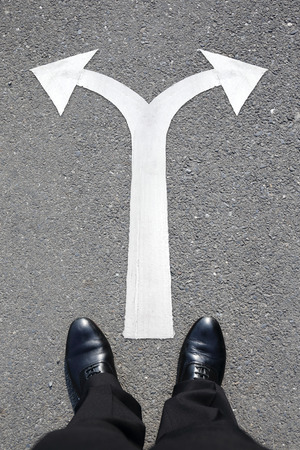 road worker: choice concept - business man walking with arrow on the road Stock Photo