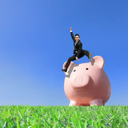 Happy Saving Money with my piggy bank - Young excited business man jump over piggy bank photo