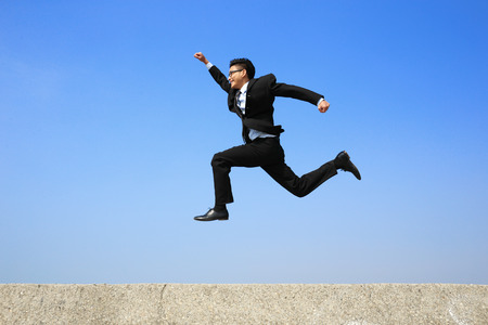 hurry up: business man running with blue sky background, full length, asian male