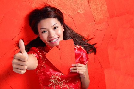 chipao: happy chinese new year. Smile woman lying on red envelope bed, high angle view