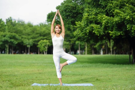 people and nature: Young sport girl do yoga in the park, asian beauty woman