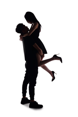 lovers embracing: silhouette of two lovers. Isolated on white background